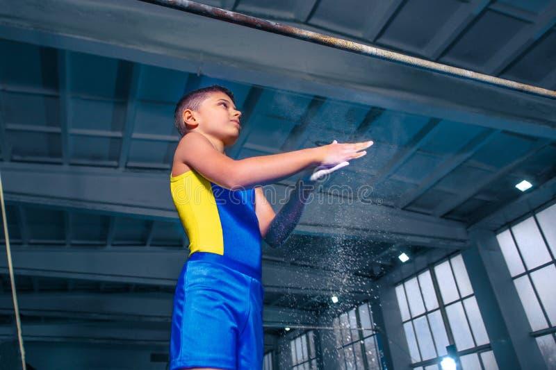 O menino bonito é contratado na ginástica dos esportes no barras paralelas imagem de stock
