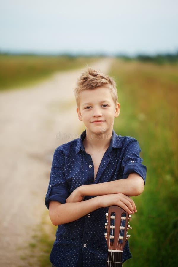 O menino bonito considerável está guardando a guitarra acústica em exterior fotografia de stock royalty free