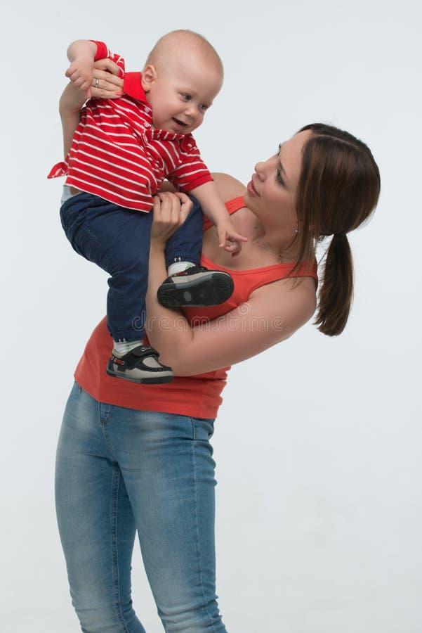 O menino bonito da criança é impertinente nas mãos das mamãs imagens de stock