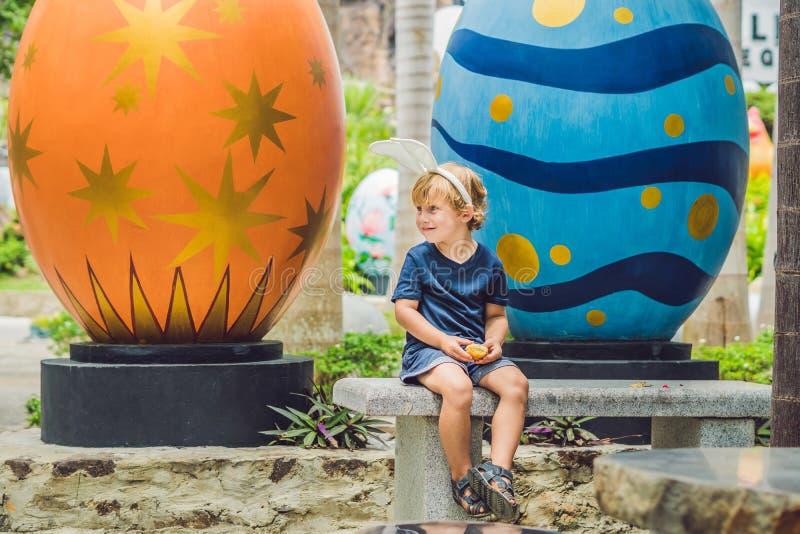 O menino bonito da criança com as orelhas do coelho que têm o divertimento com ovos da páscoa tradicionais caça, fora Comemorando fotos de stock royalty free