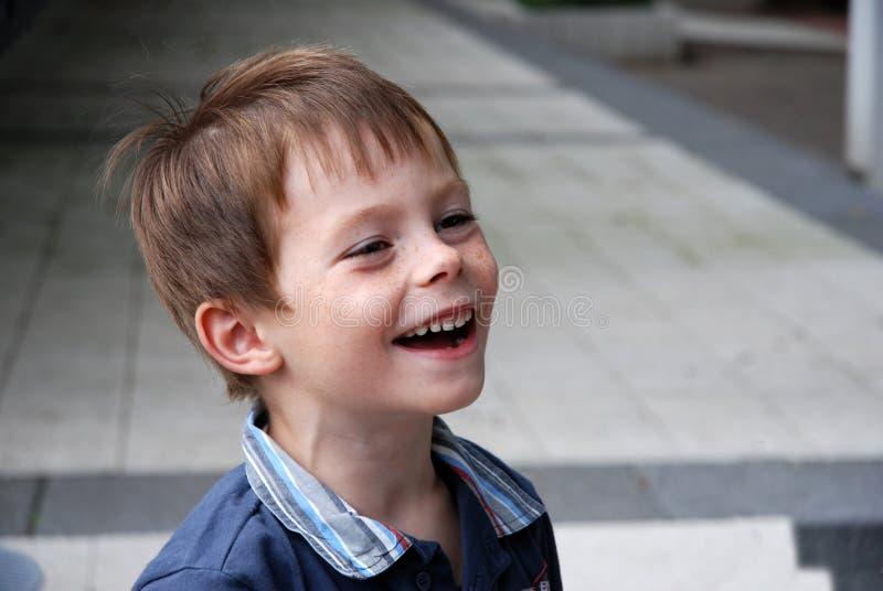 O menino bonito do jardim de infância ri heartily imagem de stock royalty free