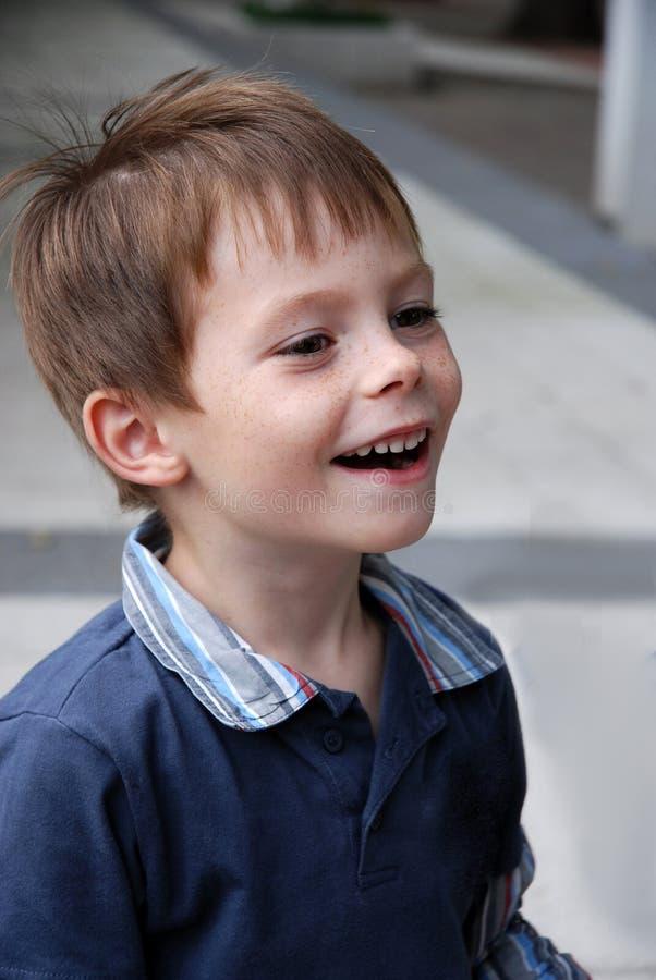 O menino bonito do jardim de infância ri heartily fotografia de stock