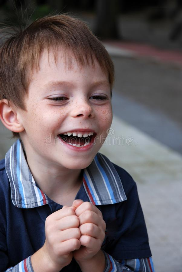 O menino bonito do jardim de infância ri heartily fotos de stock