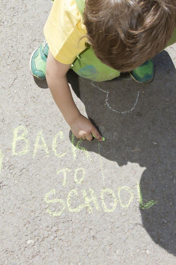 O menino bonito escreve com gizes coloridos em um pavimento o suspiro de volta à escola A criança tira em um asfalto com gizes Es imagem de stock royalty free