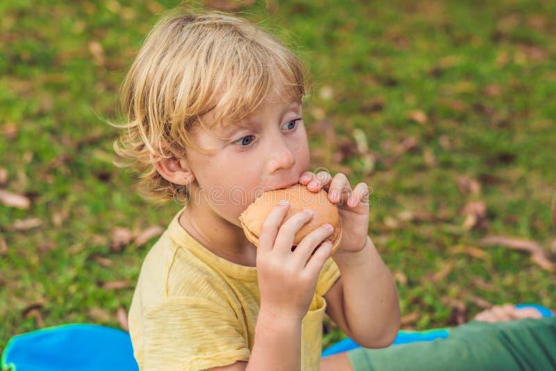 O menino bonito está comendo o close up saboroso grande do Hamburger foto de stock royalty free