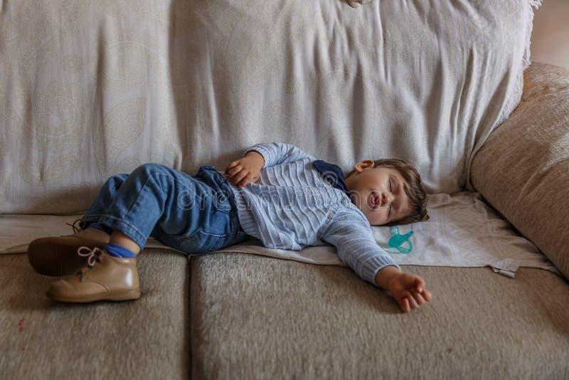 O menino bonito está dormindo pacificamente no sofá na sala de visitas de sua casa fotos de stock