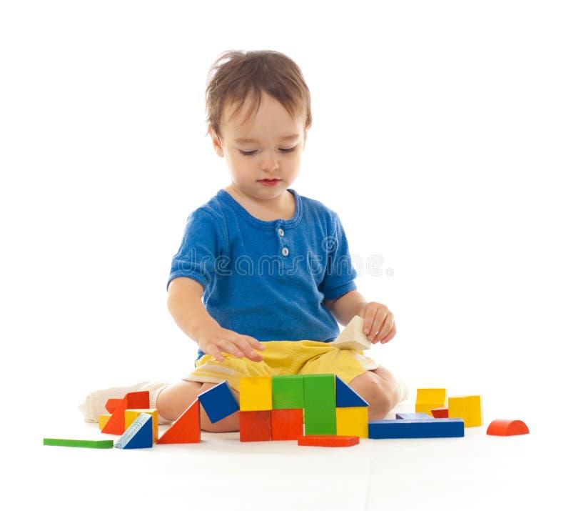 O menino bonito está jogando com blocos de apartamentos coloridos fotos de stock