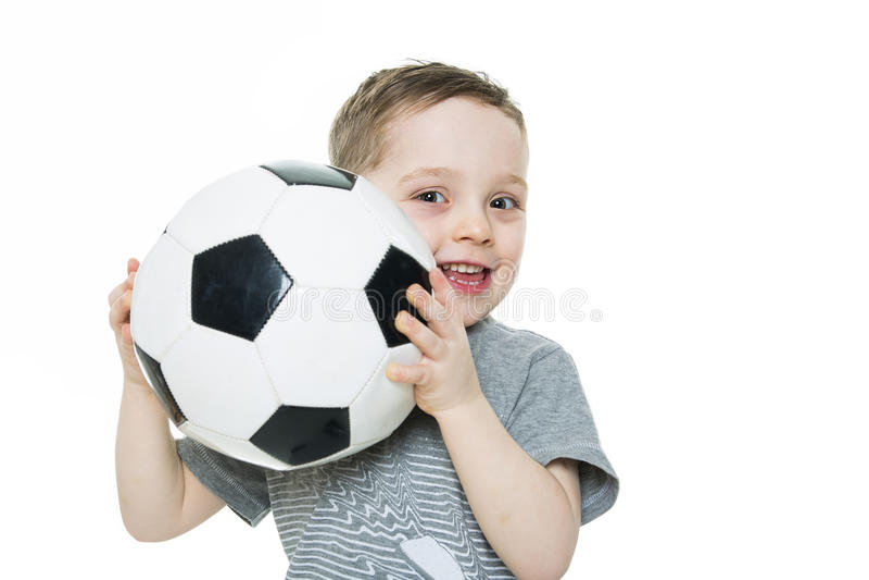 O menino bonito está mantendo uma bola do futebol isolada no fundo branco Futebol foto de stock royalty free