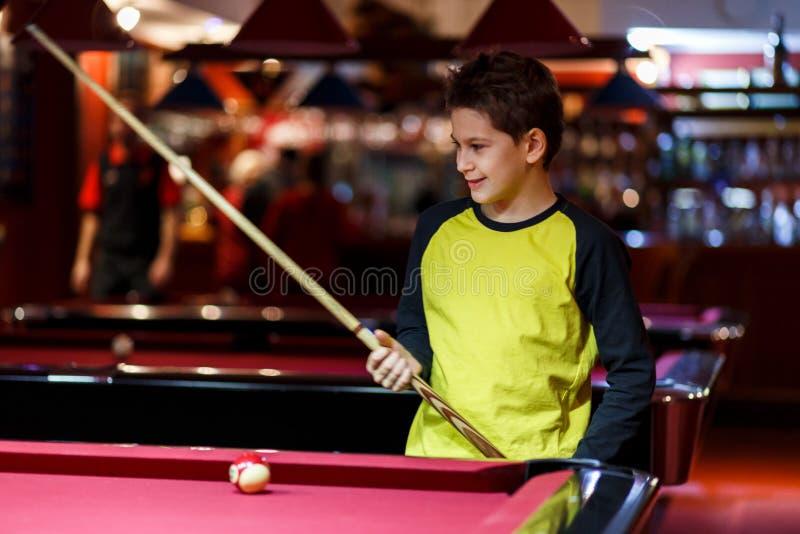 O menino bonito na camisa amarela de t joga o bilhar ou a associação no clube A criança aprende jogar a sinuca Menino com sugestã fotografia de stock royalty free