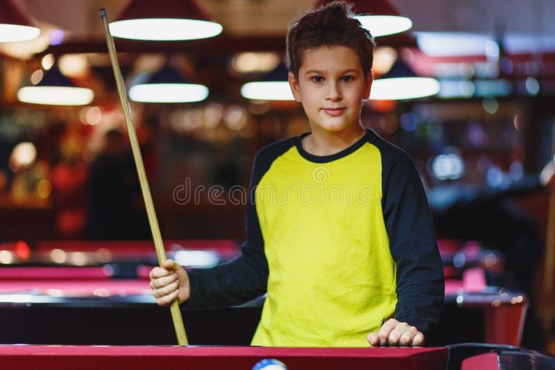 O menino bonito na camisa amarela de t joga o bilhar ou a associação no clube A criança aprende jogar a sinuca Menino com sugestã imagens de stock