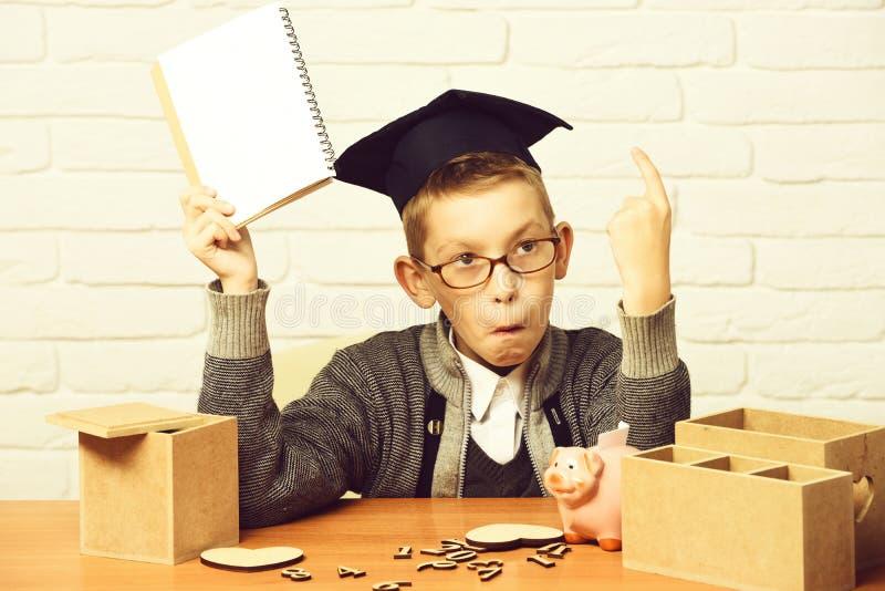 O menino bonito novo do aluno na camiseta cinzenta e os vidros que sentam-se na mesa com números de madeira do caderno à disposiç imagens de stock