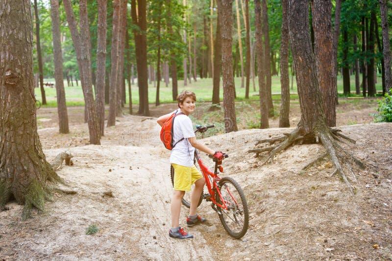O menino bonito novo no capacete monta uma bicicleta no parque O menino vai na estrada esporte fotos de stock