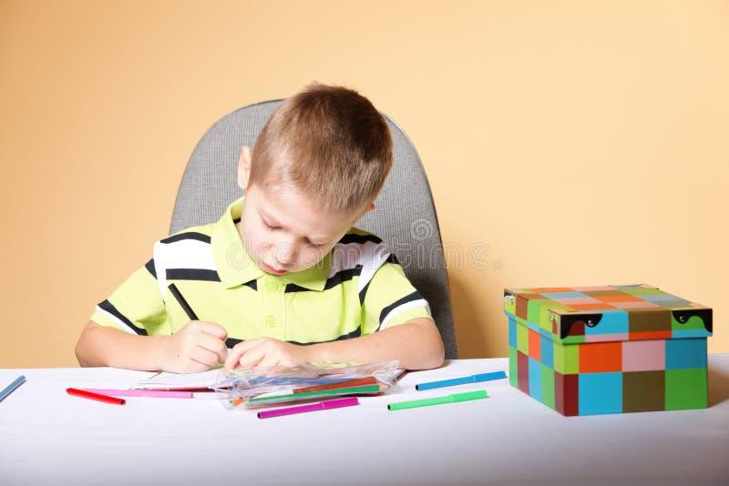 O menino bonito novo tira com lápis da cor fotos de stock