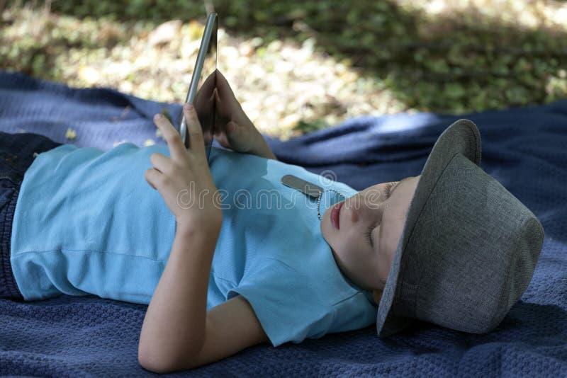 O menino bonito pequeno da idade pré-escolar, com um chapéu, está encontrando-se na GR fotos de stock royalty free