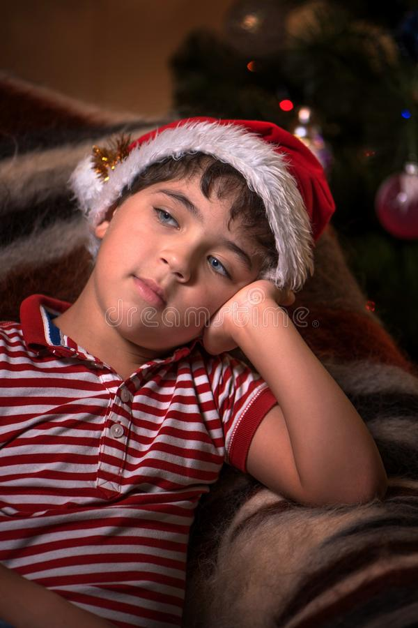 O menino bonito pequeno no chapéu de Santa está sonhando para um presente fotos de stock royalty free