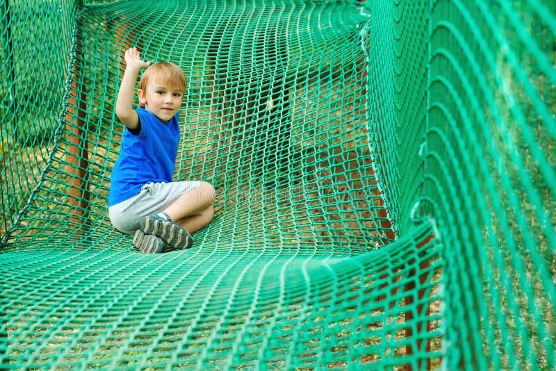 O menino bonito supera obstáculos no parque da aventura da corda Conceito das f?rias de ver?o Criança feliz que joga no parque da imagens de stock