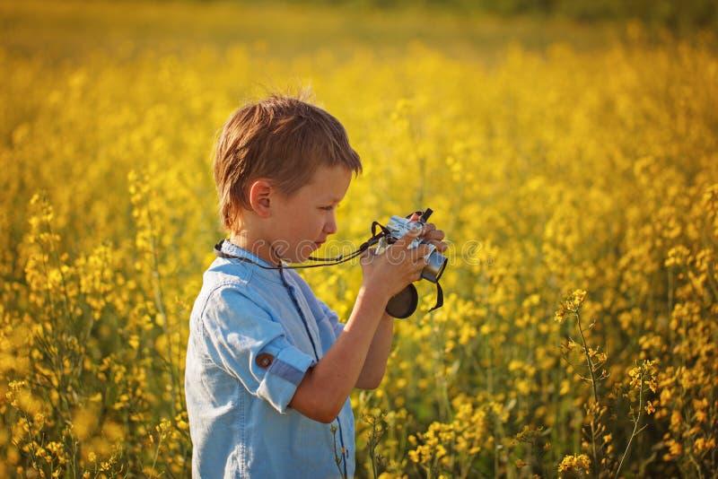 O menino bonito toma imagens das flores em um campo amarelo no verão foto de stock