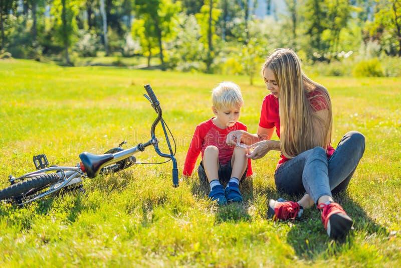 O menino caiu a bicicleta, suas pastas da mãe um emplastro em seu joelho imagens de stock royalty free