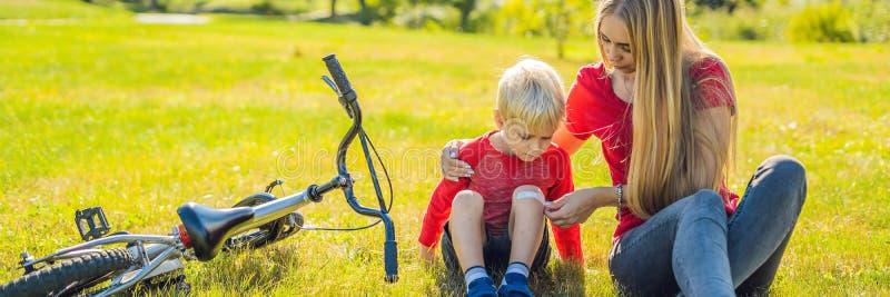 O menino caiu a bicicleta, suas pastas da mãe um emplastro em sua BANDEIRA do joelho, formato longo imagem de stock royalty free