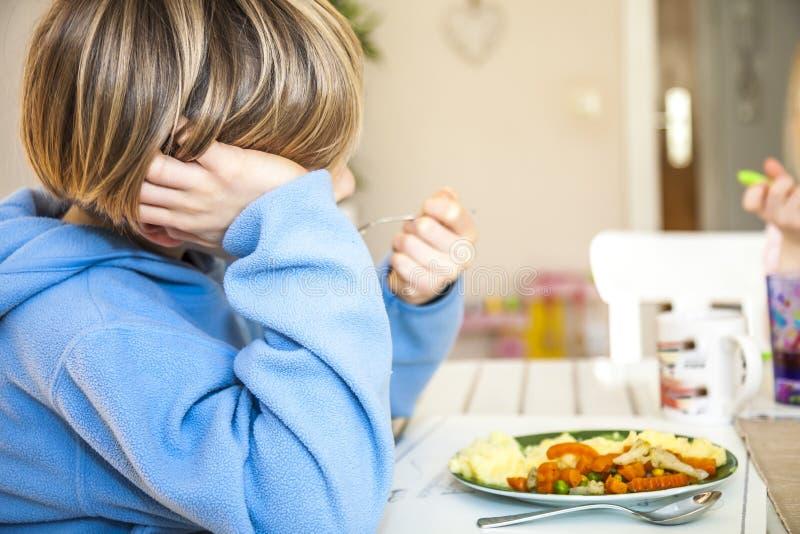 O menino cansado não gosta de comer seu almoço fotos de stock