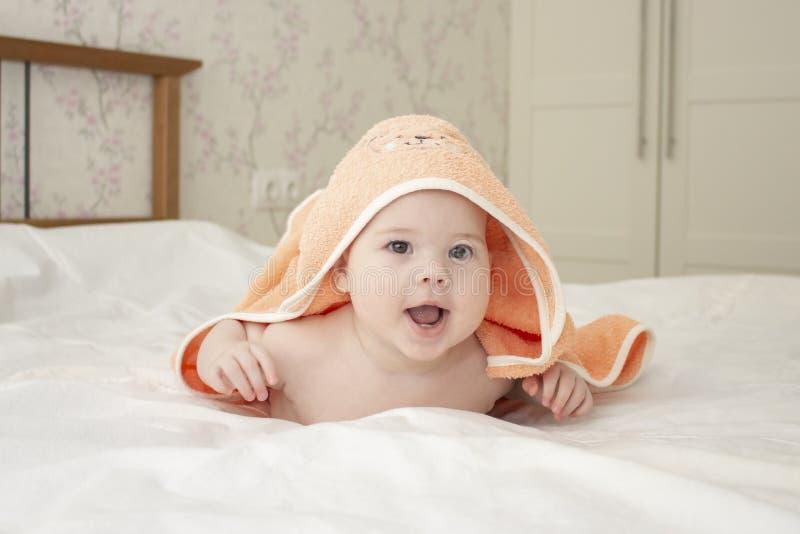 O menino caucasiano da menina do bebê 5 meses rasteja para fora sob a toalha, boca aberta de riso alegre, foco macio fotografia de stock