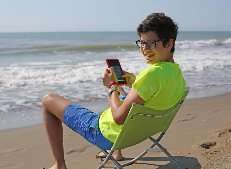 O menino caucasiano de sorriso dos jovens lê um ebook que senta-se na praia imagens de stock