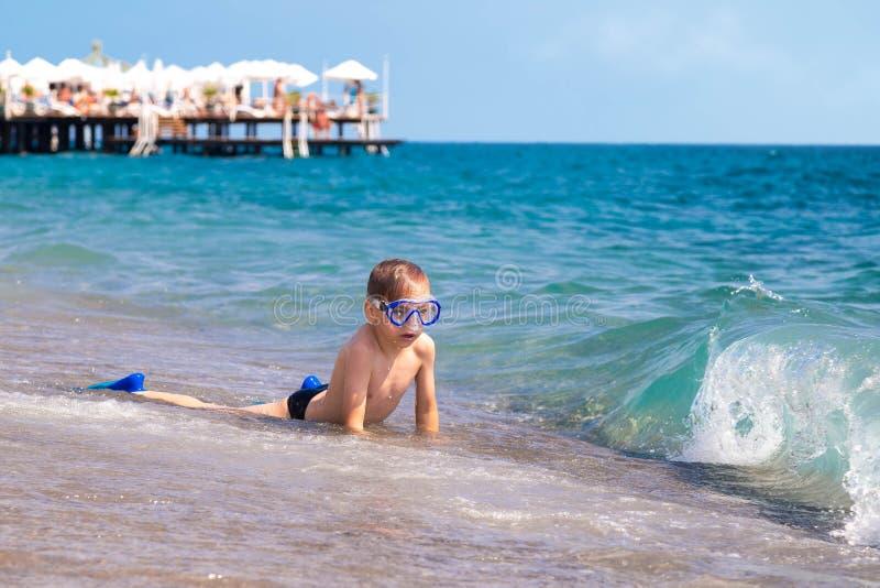 O menino caucasiano em uma tira da ressaca no litoral em uma máscara e em um tubo, toma sol e espera uma onda grande no verão foto de stock royalty free
