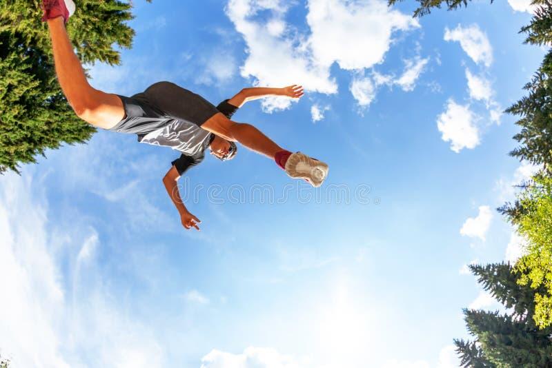 O menino caucasiano faz um salto em um prado da montanha Vista de baixo de fotos de stock