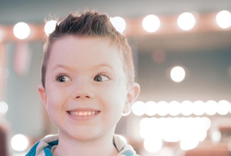 O menino caucasiano feliz pequeno está sorrindo após o corte do cabelo foto de stock