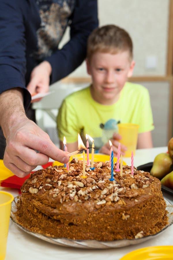 O menino caucasiano feliz que comemora seu aniversário e apronta-se para fundir velas no bolo cozido caseiro fotografia de stock