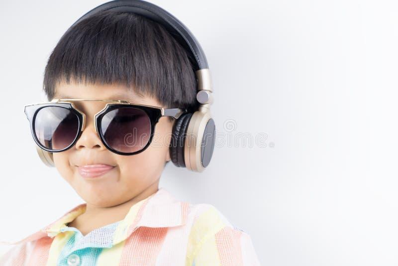 O menino com óculos de sol é escuta o fones de ouvido da música isolado imagem de stock