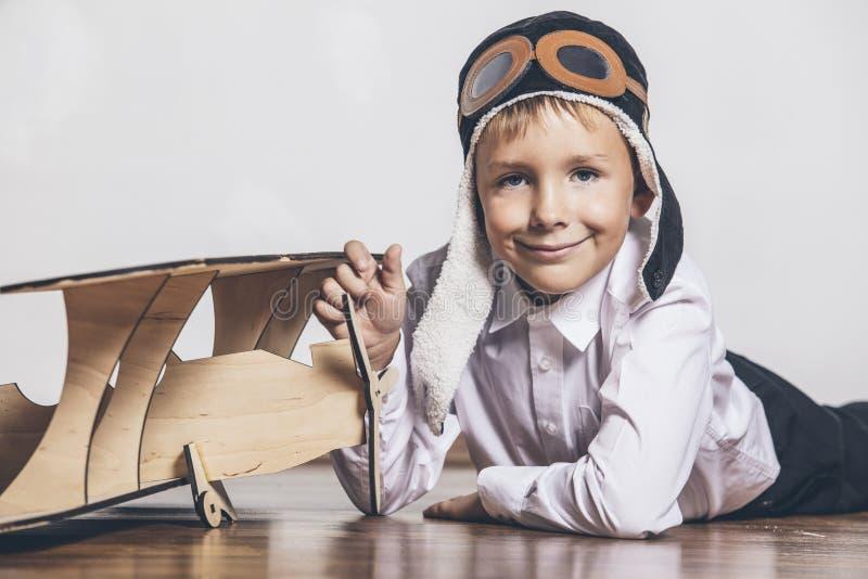 O menino com modelo plano de madeira e um tampão com tampão projeta foto de stock royalty free