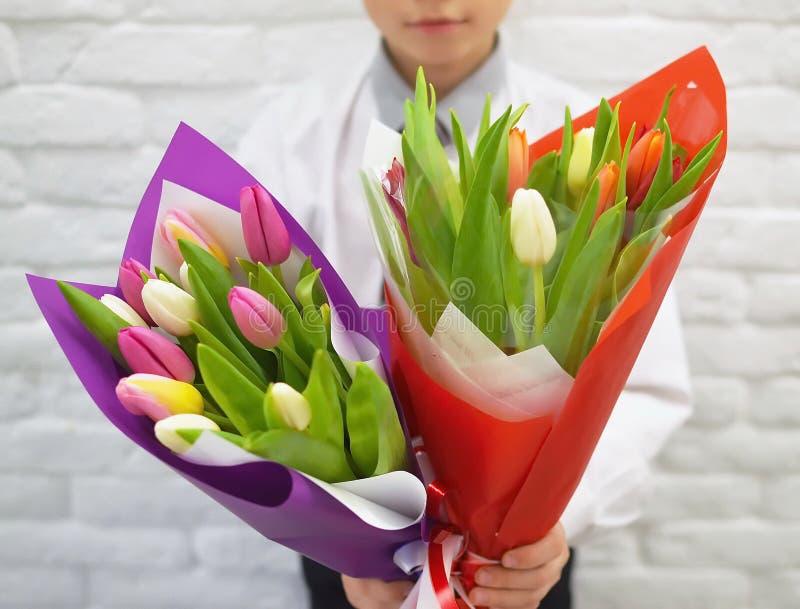 O menino com os ramalhetes bonitos das tulipas imagens de stock royalty free