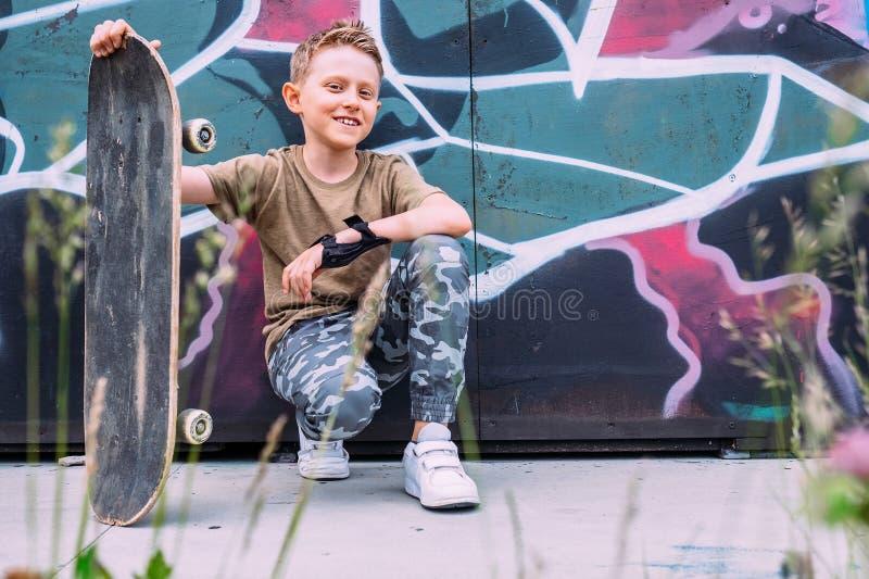 O menino com skate senta-se perto da parede pintada grafittis imagem de stock