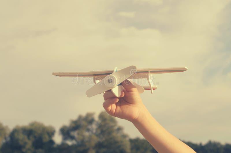 O menino com sua mão corre o modelo do plano no céu fotografia de stock