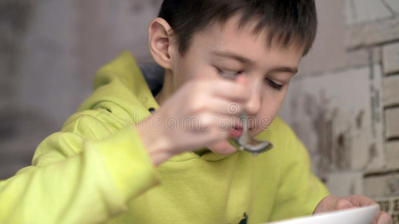 O menino com um apetite come a sopa, tem o divertimento imagem de stock