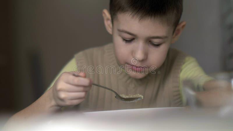 O menino com um apetite come a sopa, tem o divertimento imagens de stock royalty free