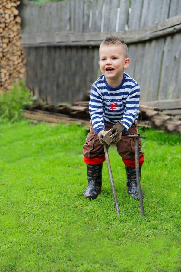 O menino com um martelo do ferro para conduzir uma haste de metal fotos de stock royalty free
