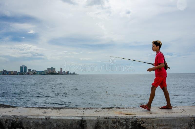 O menino com vara de pesca anda ao longo da paredão em Havana foto de stock