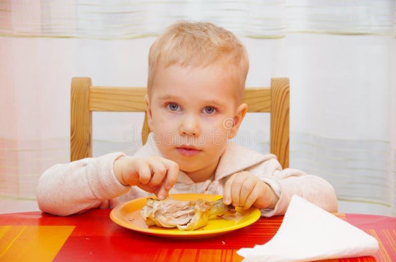 O menino come a galinha imagem de stock