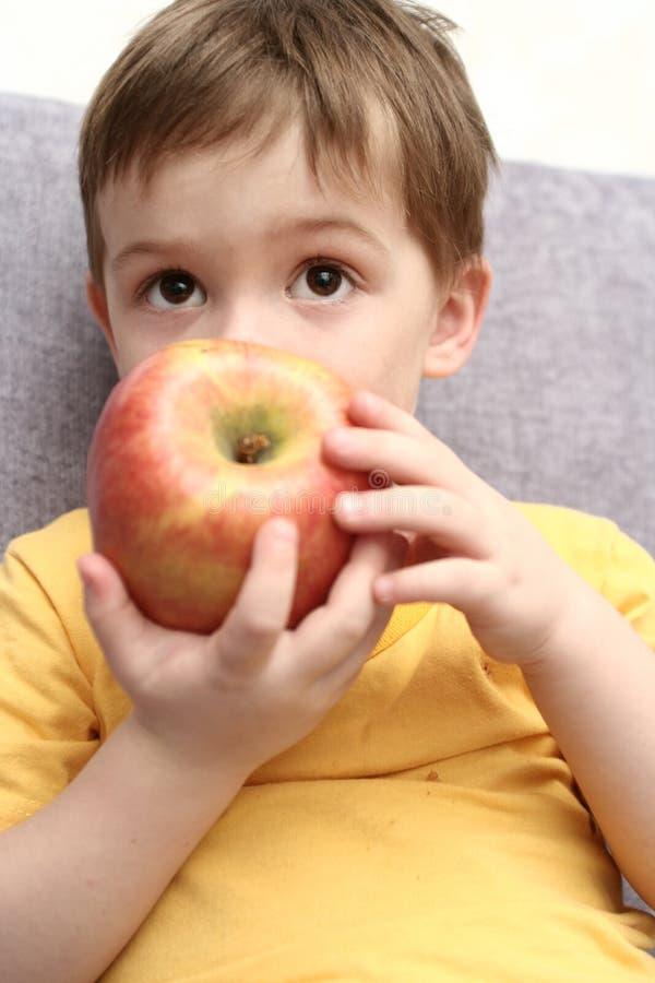 O menino come a maçã vermelha grande fotografia de stock royalty free