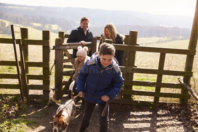 O menino conduz seus família e cão através de uma porta no campo fotos de stock royalty free