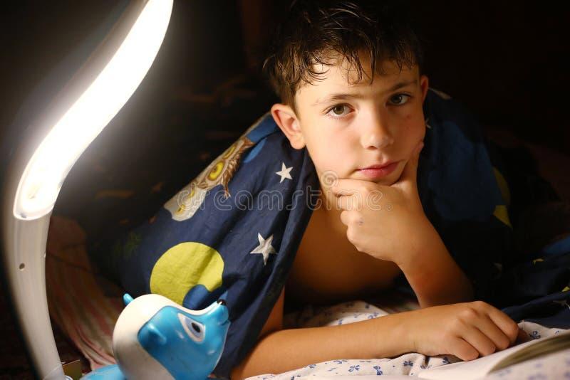 O menino considerável do Preteen leu o livro com a lâmpada antes do sono fotos de stock royalty free