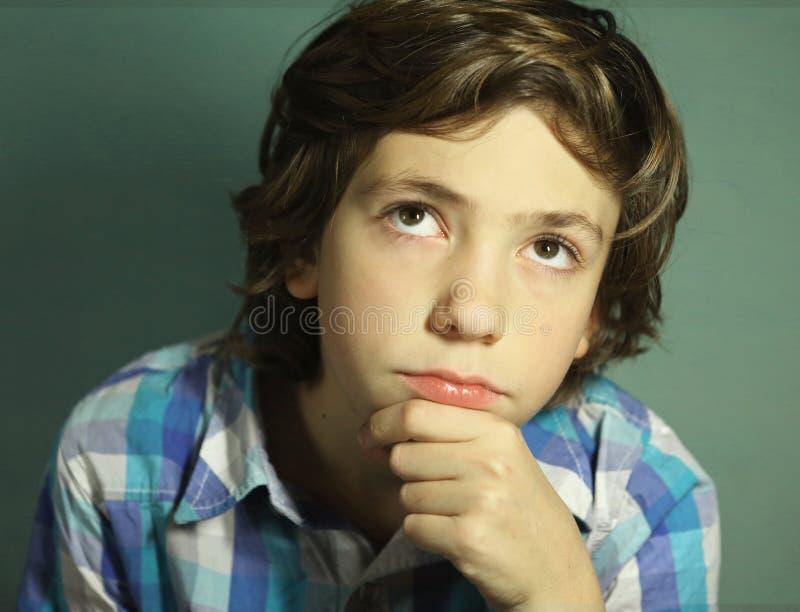 O menino considerável do Preteen pensa sobre a questão difícil imagens de stock royalty free