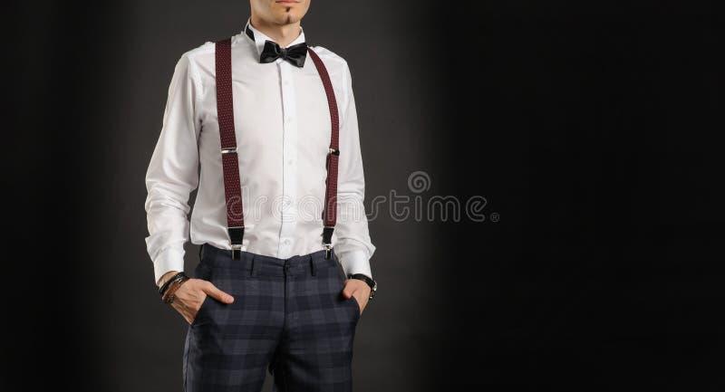 O menino considerável novo na camisa branca com laço, couse vê, cronometra disponível imagens de stock royalty free