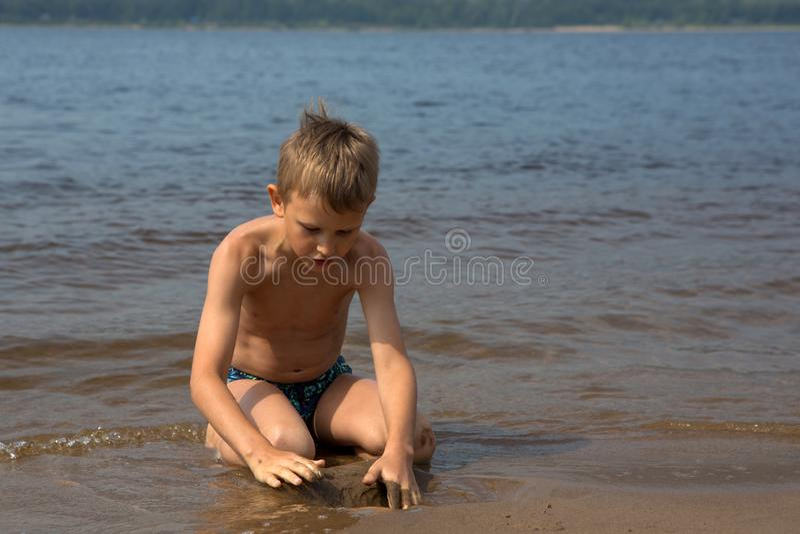 O menino constrói figuras da areia na praia fotografia de stock royalty free