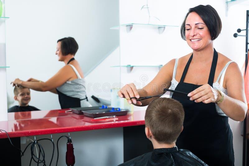 O menino contente que obtém o cabelo cortou pelo cabeleireiro da mulher imagem de stock