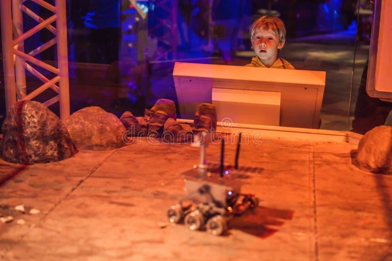 O menino controla o vagabundo do brinquedo em Marte Voo ao conceito de Marte foto de stock