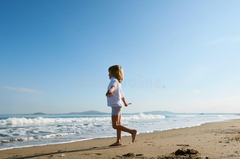 O menino corre para fora para encontrar o mar foto de stock