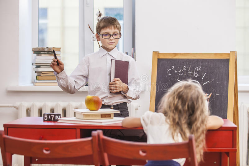 O menino, crianças da menina na escola tem um feliz, curioso, esperto fotos de stock royalty free